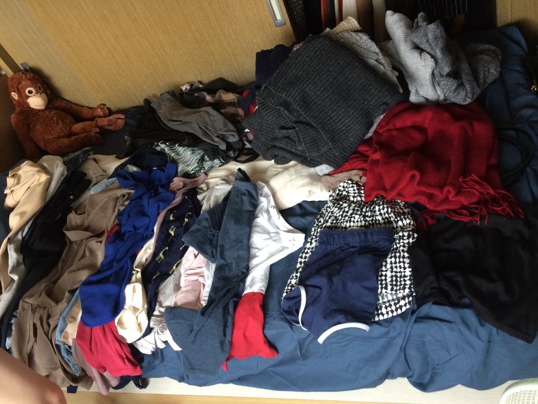 格子櫃中的衣物先全部拿出來在床上分類。