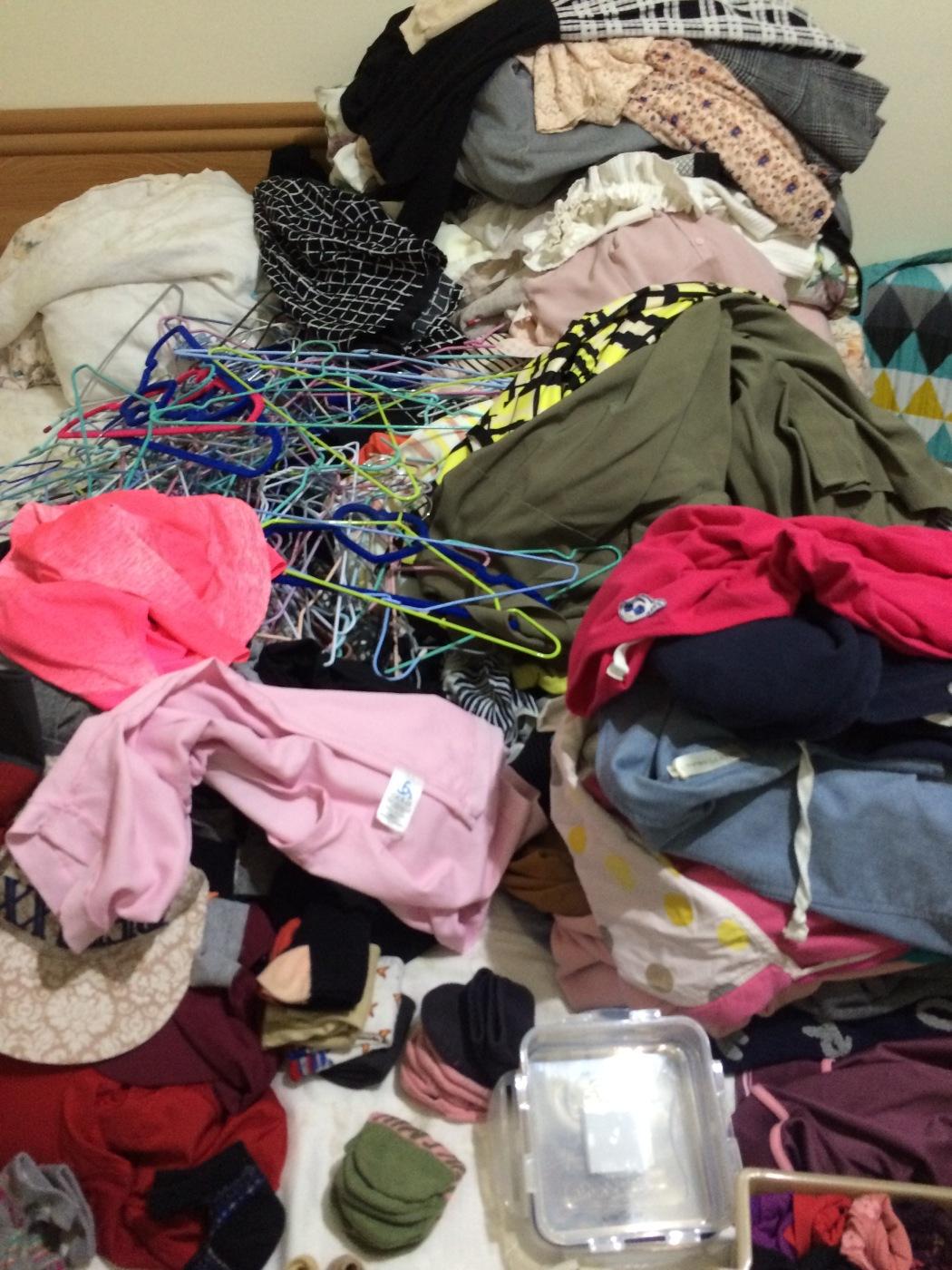 跟委託人一起把所有衣服全部集中在床上,堆成一座山